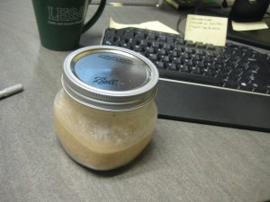 overnight oats in ball jar on desk with computer